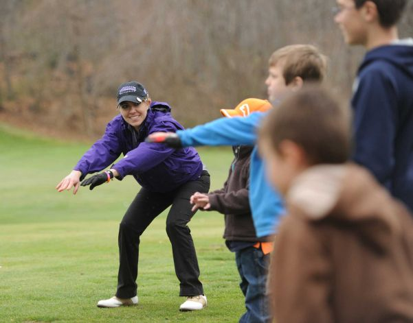 Monique Gesualdi, of Danbury, stretches out with children while helping teach a kids golf lesson at Richter Park Golf Course in Danbury, Conn. Tuesday, April 29, 2014. Gesualdi underwent a liver transplant and two brain surgeries two years ago and had a successful recovery. She now helps out with childrens golf lessons at Richter Park and hopes to teach golf professionally someday. Photo: Tyler Sizemore